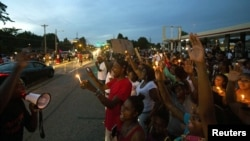 US -- People line up in the street during a peaceful demonstration, as communities react to the shooting of Michael Brown in Ferguson, Missouri August 14, 2014.