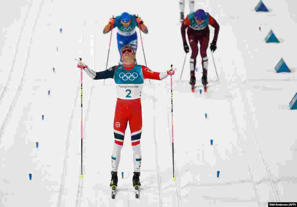 Біг на лижах: норвежець Йоганнес Гесфлот Клебо (в центрі) святкує перемогу, перетнувши фінішну лінію, він виборов золото. Срібну позицію посів італієць Федеріко Пеллеґріно ліворуч позаду. А Олександр Большунов із Росії отримав третє місце у чоловічому фіналі класичного лижного бігу