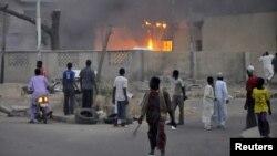 Жарылыстан кейінгі өртке қарап тұрған адамдар. Нигерия, 20 қаңтар 2012 жыл. (Көрнекі сурет)