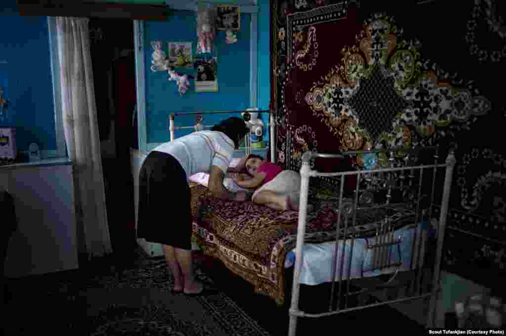 Anoush Gasparyan watches her five year old sleeping daughter Anahid in their home in the village of Myasnikyan. The family, which is struggling after a series of accidents and health issues including snake bite and lightning strikes, receives help from the diaspora-based Children of Armenia Fund (COAF). COAF was founded by Istanbul-born, American-based Armenian Dr. Garo Armen, who was struck by the depths of poverty in the Aramir region of Armenia and resolved to do something about it. The organization, which is largely supported by Diasporan Armenians, mostly funds schools, but also assists in providing a more comprehensive social care to the families of the village children.