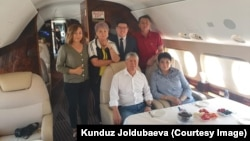 Former Kyrgyz President Almazbek Atambaev (seated left) and his associates head to Moscow aboard a private jet on July 24.