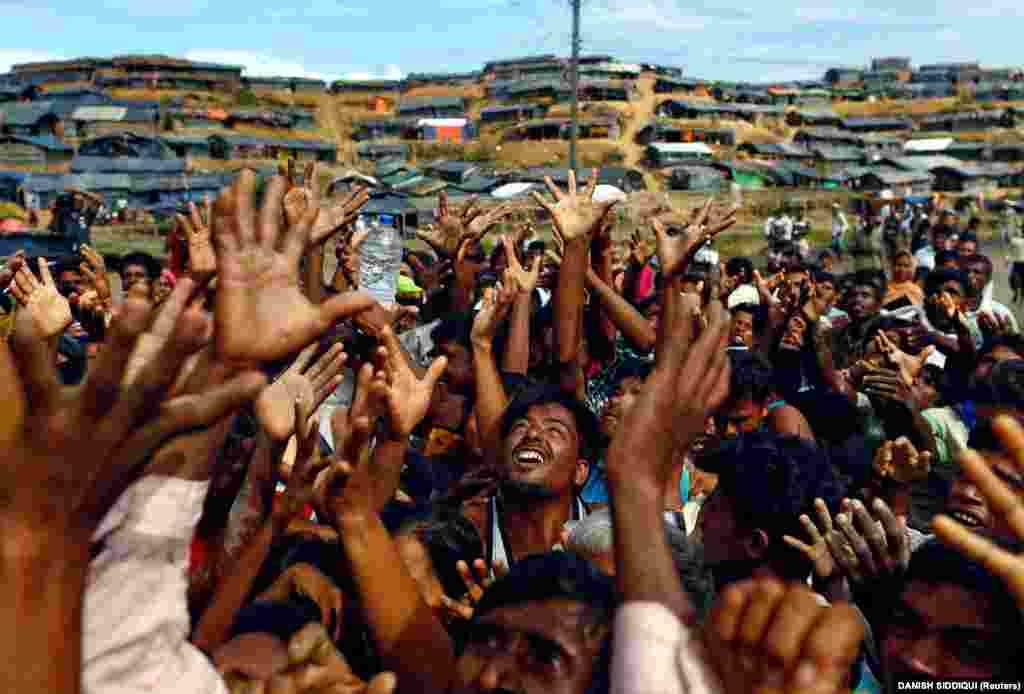 Rohingya refugees from Burma stretch their hands to receive aid distributed by local organizations at the Balukhali makeshift refugee camp in Cox's Bazaar, Bangladesh. (Reuters/Danish Siddiqui)