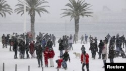 People walk along a snow covered street in the Adriatic port city of Split.