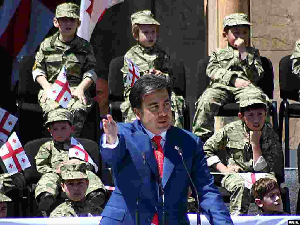 """სამხედრო აღლუმის დაწყებამდე პრეზიდენტმა სიტყვით მიმართა რუსთაველის გამზირზე შეკრებილებს. - პრეზიდენტთან ერთად აღლუმი მიიღეს პატარა """"ჯარისკაცებმაც""""."""