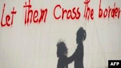 """Silueta djece pored zida na kojem je ispisan grafit """"Dopustite im da pređu granicu"""", zabilježeno nedaleko od mjesta Idomeni, Makedonija, maj 2016."""