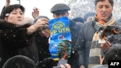"Лидеры и активисты партии ОСДП жгут плакаты президентской партии ""Нур Отан"". Алматы, 17 января 2012 года."