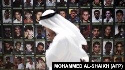 یک شهروند از کنار تصاویر کسانی که گفته میشود بازداشت شدهاند رد میشود؛ منامه، ژوئیه ۲۰۱۵