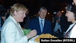 Канцлер Германии Ангела Меркель (слева) и президент Кыргызстана Алмазбек Атамбаев (в центре). Бишкек, 14 июля 2016 года.