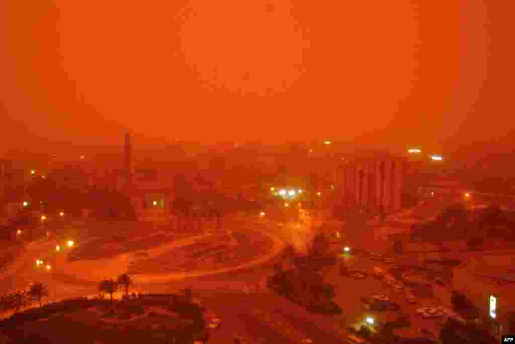 A sand storm hits the center of Baghdad, which is also shrouded in smoke from burning oil trenches.