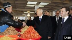 Uzbek President Islam Karimov (center) and his Russian counterpart, Dmitry Medvedev (right), visit a local market in Tashkent.