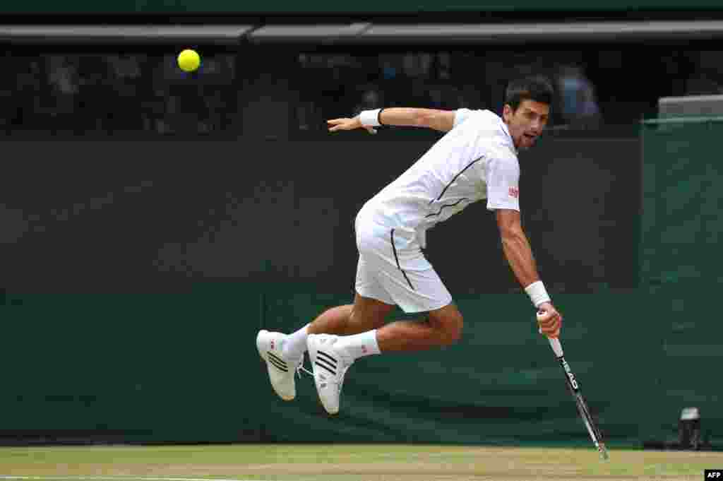 Serbia's Novak Djokovic returns a shot against the Czech Republic's Tomas Berdych during their men's singles quarterfinal match at the 2013 Wimbledon championships in London. (AFP/Carl Court)