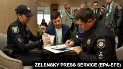"""Poliția îl amendează pe Volodimir Zelenski pentru """"încălcarea secretului votului"""", după ce demonstrase în public buletinul de vot. Codul electoral prevede pentru o asemenea încălcare inclusiv pedeapsa cu închisoarea. Kiev, 21 aprilie 2019"""