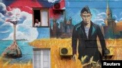 Житель Севастополя выглядывает из окна, в стена его дома украшена политическим настенным рисунком. Май 2014 года