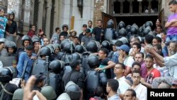 Police move into a mosque during clashes with supporters of deposed Egyptian President Muhammad Morsi inside a room of the Al-Fath Mosque in Cairo on August 17.