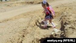 Ауылға тартылып, аяқсыз қалған су құбырының үстімен мектепке бара жатқан балалар. Шұбарши кенті, Ақтөбе облысы. 14 мамыр 2012 жыл.