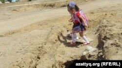 Ребенок перешагивает через канаву, в которой проложены трубы, так и не подключенные к водопроводу. Село Шубарши Актюбинской области.