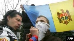 Un protestatar din Moldova scrie un slogan pe o mască ce acoperă fața, 10 aprilie 2009, Chișinău