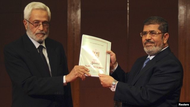 Constituent assembly chairman Hossam El-Gheriany gave President Muhammad Morsi (R) the final constitutional draft on December 1.