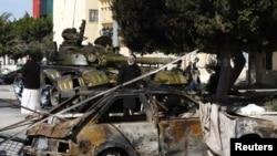 Людзі ідуць за танкам, на якім вайскоўцы Кадафі, якія перайшлі да паўстанцаў, у горадзе Завія, у 50 км на захад ад Трыпалі. Лібія, 5 сакавіка 2011 г.