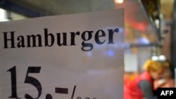 A sign in a restaurant window shows the price of a hamburger in outgoing Estonian kroons and euros.