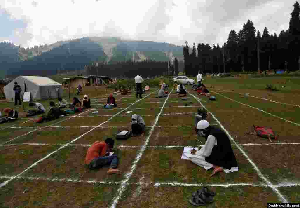 Вчителі та діти на безпечній дистанції під час уроку на відкритому повітрі на мальовничій гірській станції Даудхпатрі в районі Будгам у центральному Кашмірі, 24 серпня