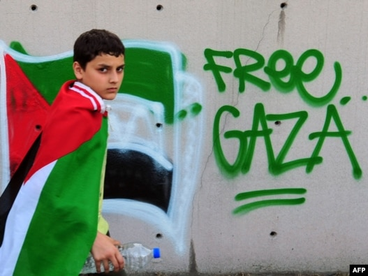 A boy wears a Palestinian flag during an anti-Israeli protest in front of the Israeli Consulate in Istanbul