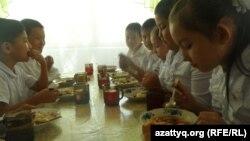 Мектеп асханасында тамақ ішіп отырған оқушылар. (Көрнекі сурет)
