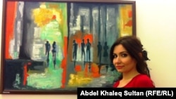 الفنانة هبه يونس أمام احدى لوحاتها