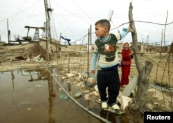 Баку іргесіндегі мұнай кеніші жанында ойнап жүрген балалар. Әзербайжан, 8 қараша 2005 жыл.