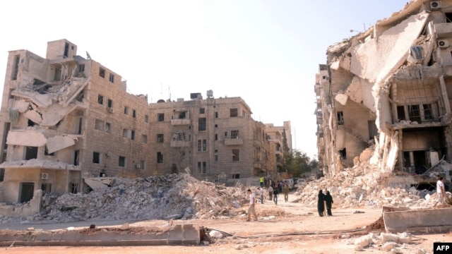 Syria -- People walk past a row of destroyed buildings near the Al-Hayat Hospital in the northern city of Aleppo, 10Sep2012