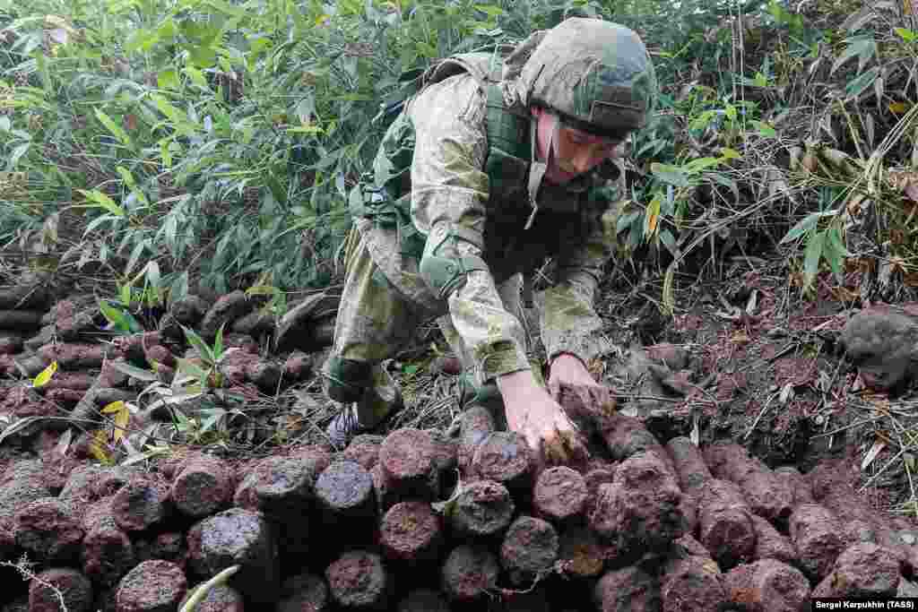 A member of the expedition in military uniform stacks the artillery shells. Handling such time-ravaged ordnance is risky, as detonators inside can decay over time, leaving the explosive on a hair trigger. In 2010, three experienced disposal experts were killed in Germany while trying to defuse a WWII-era bomb.