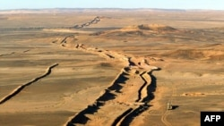 An earthen wall divides the Western Sahara into two parts.