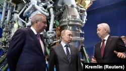 """2019 წლის 12 აპრილი: რუსეთის პრეზიდენტი ვლადიმირ პუტინი (ცენტრში), """"როსკოსმოსის"""" დირექტორი დმიტრი როგოზინი (მარცხნივ) და სარაკეტო ძრავების საწარმო """"ენერგომაშის"""" ხელმძღვანელი იგორ არბუზოვი """"ენერგომაშში"""", მოსკოვის მახლობლად"""