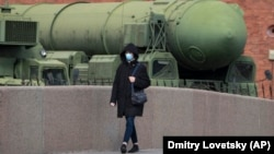 A woman wearing a face mask during a coronavirus lockdown walks past a Russian intercontinental ballistic missile launcher displayed at the Artillery Museum in St. Petersburg.