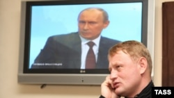 Former police Major Aleksei Dymovsky walks past a video screen showing Prime Minister Vladimir Putin.