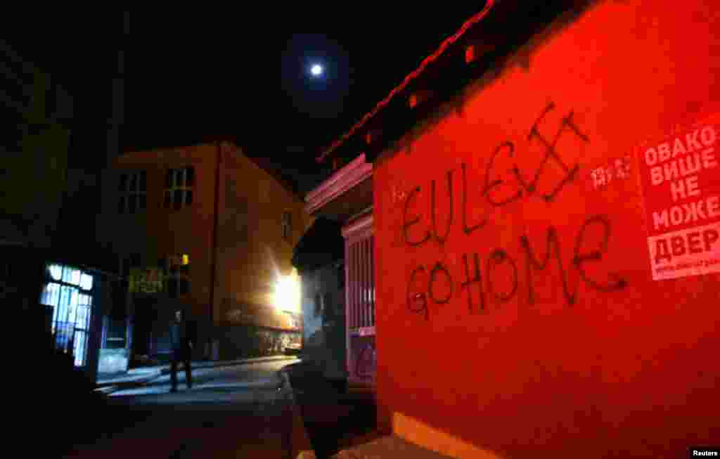 "A spray-painted slogan reads, ""Eulex go home,"" referring to the EU police mission in Kosovo."