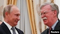 Russian President Vladimir Putin (left) shakes hands with U.S. national-security adviser John Bolton in Moscow.