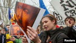 Moldovan protesters set posters depicting Russian President Vladimir Putin on fire during a rally against Russia's annexation of Ukraine's Crimea, near the Russian Embassy in Chisinau, on April 6.