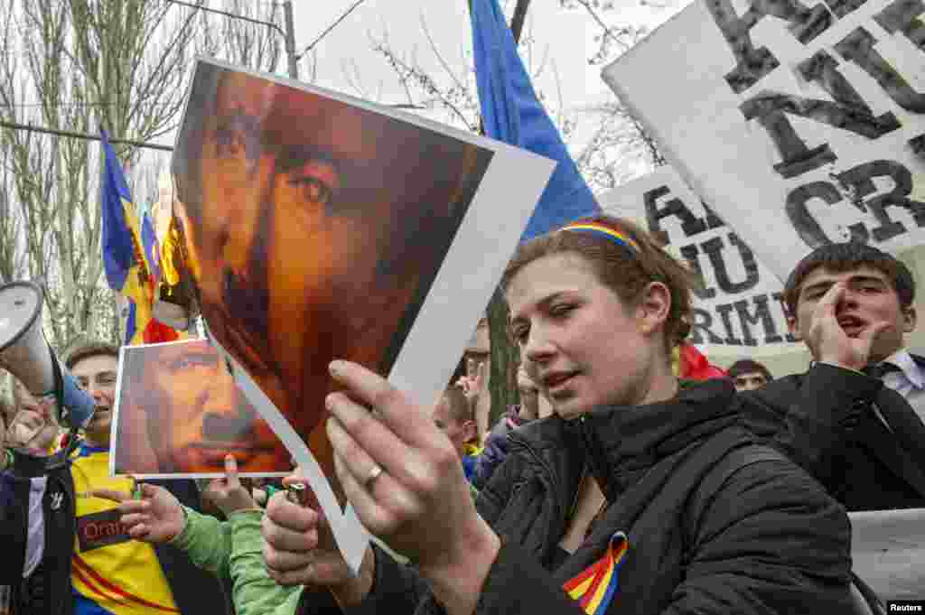 Protesters set posters depicting Russian President Vladimir Putin on fire during a rally against Russia's annexation of Ukraine's Crimea, near the Russian Embassy in Chisinau, Moldova. (Reuters/Viktor Dimitrov)