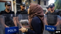 A woman holds a Ozgur Gundem newspaper in front of a police barricade in Istanbul in August.
