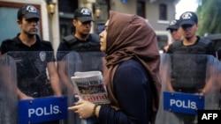 Женщина стоит с газетой в руках напротив полицейских в Стамбуле. Иллюстративное фото.