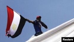 Një person e mbanë flamurin egjiptian gjatë protestave të fundit në kryeqytetin Kajro