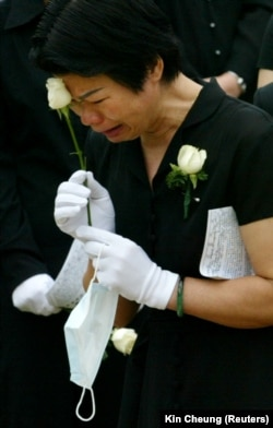 Женщина, оплакивающая медика в Гонконге, который заболел SARS и скончался в мае 2003 года после того, как вирус, вышедший из отеля Metropole, распространился на территории Гонконга.