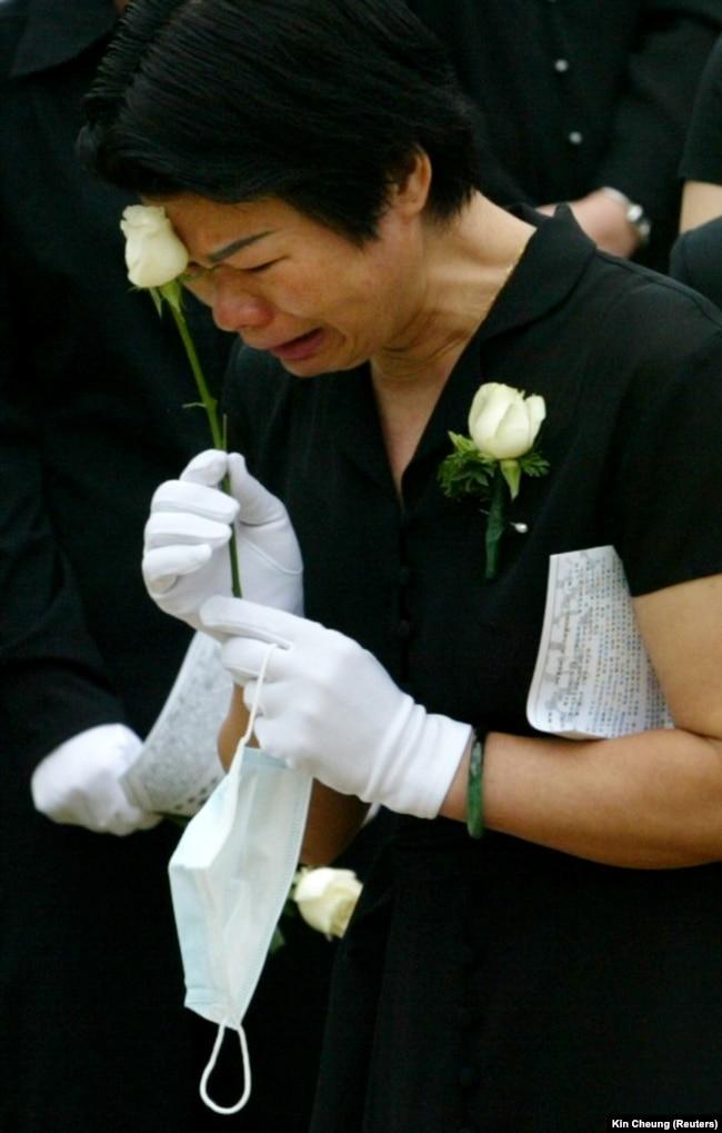 Metropole қонақүйінен Гонконг аумағына тараған SARS вирусы жұғып, 2003 жылы мамырда қайтыс болған дәрігерді жоқтап жылап тұрған әйел.