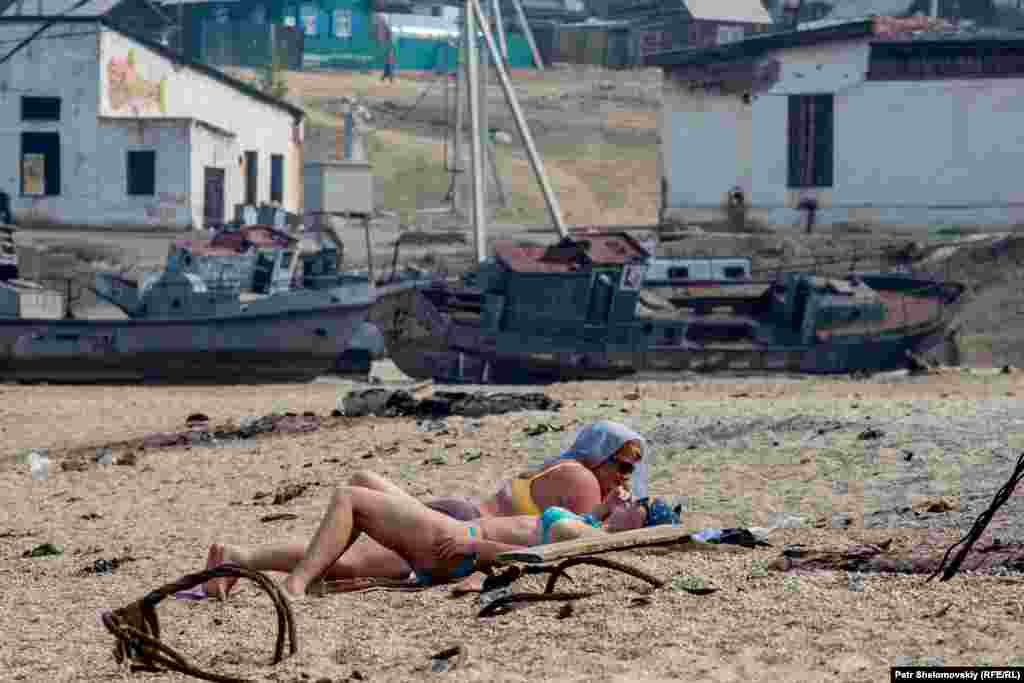 Tourists sunbathing in front of abandoned fishing vessels. The island was once home to a fish processing plant, with labor provided by prisoners of the gulag system. Now former fishing vessels are mainly used to transport summer visitors.
