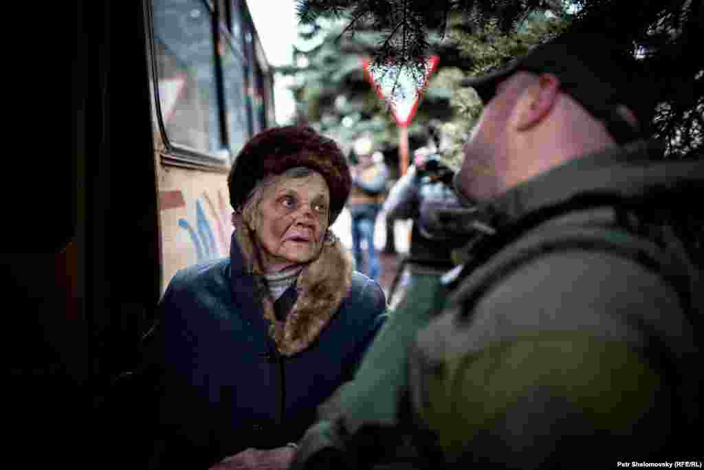 A Ukrainian army officer helps an elderly woman onto a bus leaving Debaltseve.