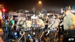 U.S. -- Police officers work to keep order as demonstrators express their feelings in Ferguson, Missouri, August 18, 2014