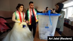 Жених и невеста на участке для голосования в городе Духок, 25 сентября 2017.