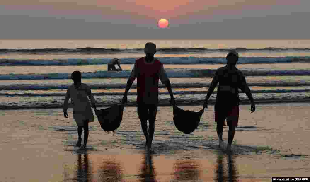 Пакістанскія рыбаловы вяртаюцца дахаты па пляжы ў Карачы.
