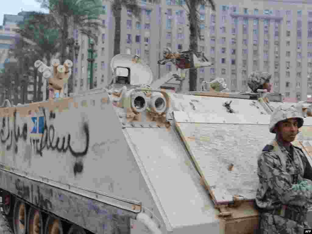 "A soldier stands guard beside an armored vehicle with the slogan ""Down Mubarak"" painted on it."